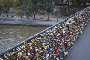 Locks lining the rails of a bridge along the River Seine