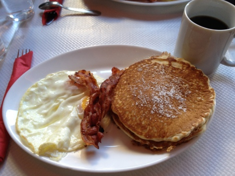Eggs, bacon, caramel pistachio pancakes, and a bottomless cup of coffee, American-style